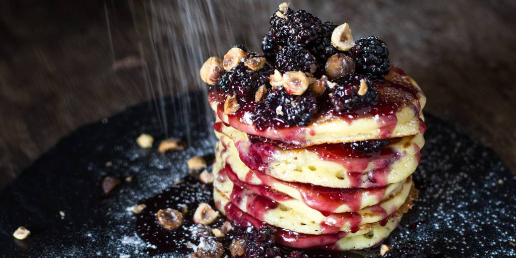 Scrumptious stack of pancakes layered with boysenberry compote and topped with hazelnuts