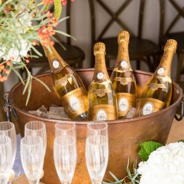 Champagne bottles in an aged copper tub with champagne flutes in the front and floral arrangements