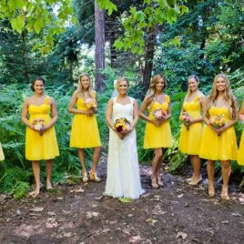 Bride and bridesmaids in yellow dresses in an outdoor setting with ferns and trees