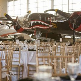 formal dinner tables and gold chairs inside the museum with airplanes in the background