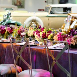 Dining tables with purple tablecloths and jewel colored floral arrangements with classic cars.