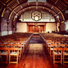 Rustic hall with vaulted ceilings set up for a wedding with an arch of flowers in front