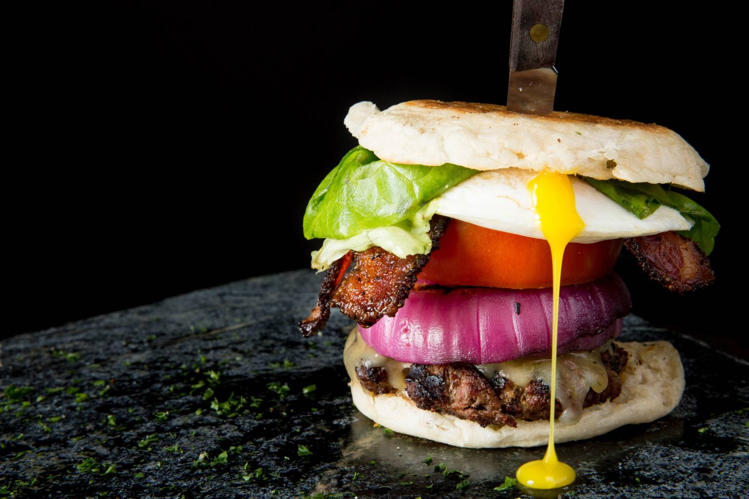 Hangover Burger with fried egg, bacon, cheese, lettuce, tomato & onion on an English muffin.