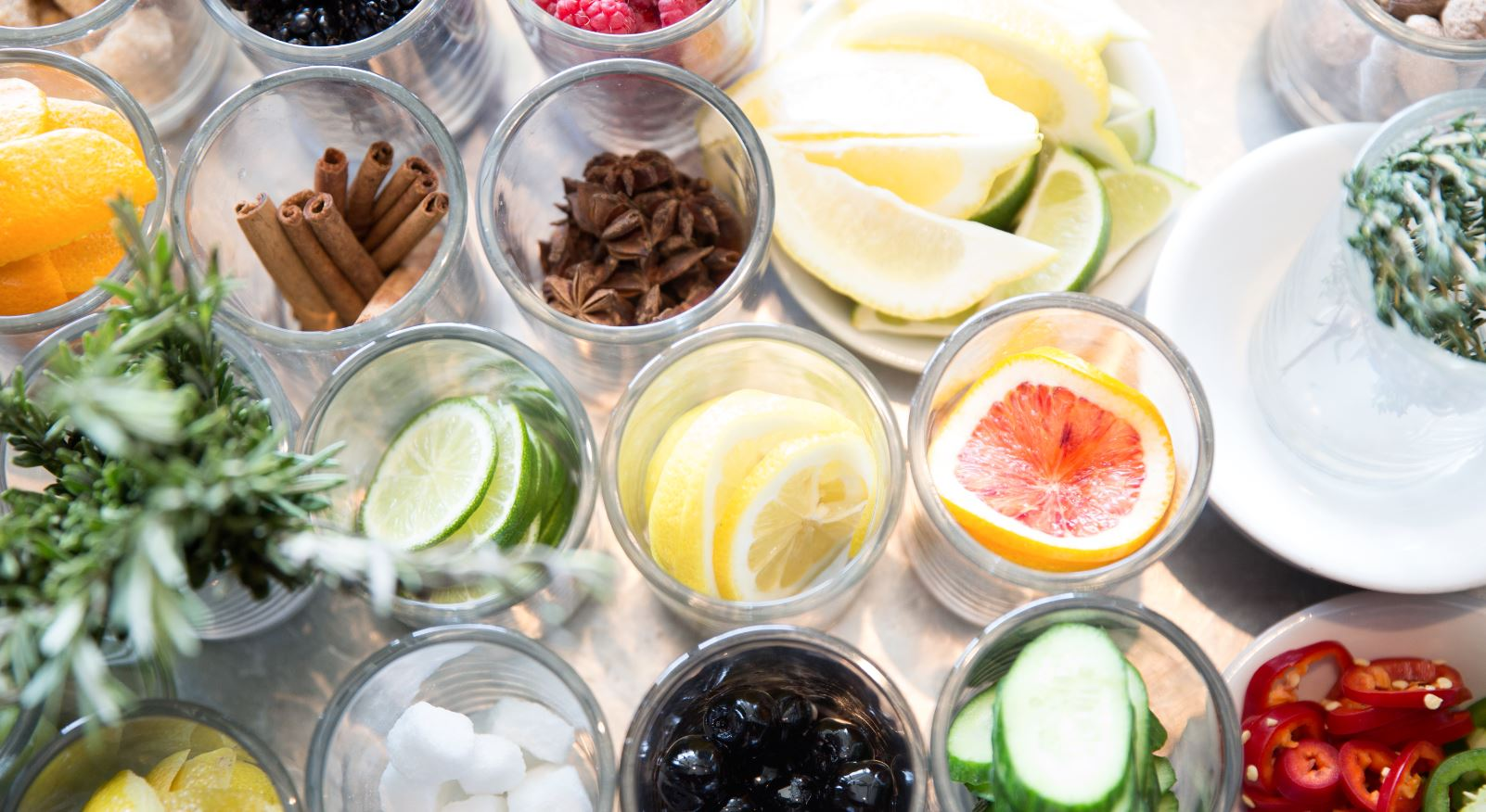 An array of fresh bar condiments with citrus slices, herbs, olives, peppers and spices.