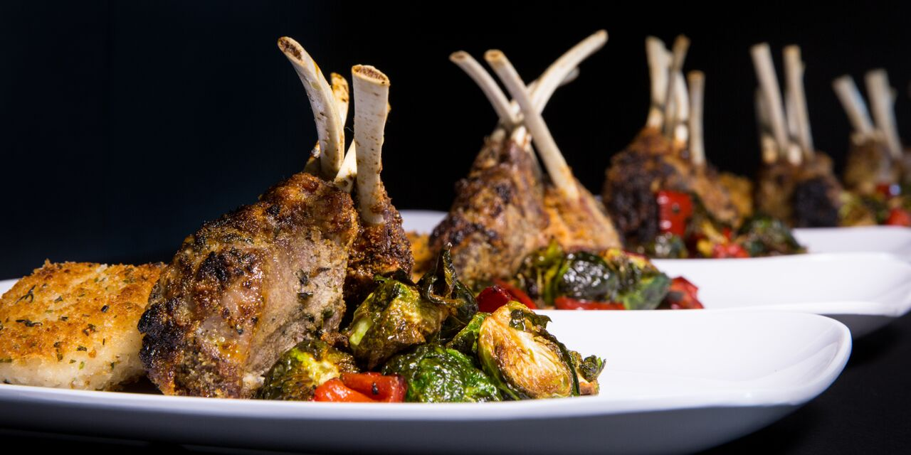 Grilled Baby Lamb Chops with grilled vegetables on a white plate against a black background